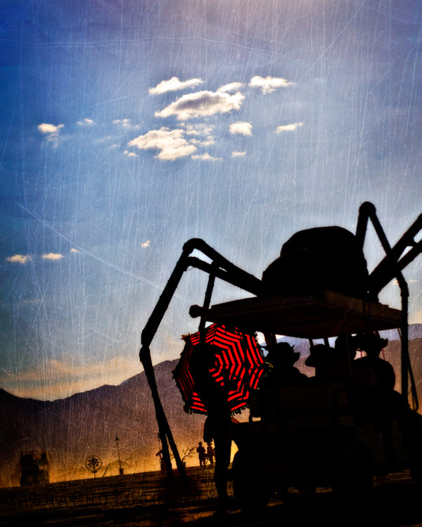 A spider art car is attracted to a girl with a red umbrella.