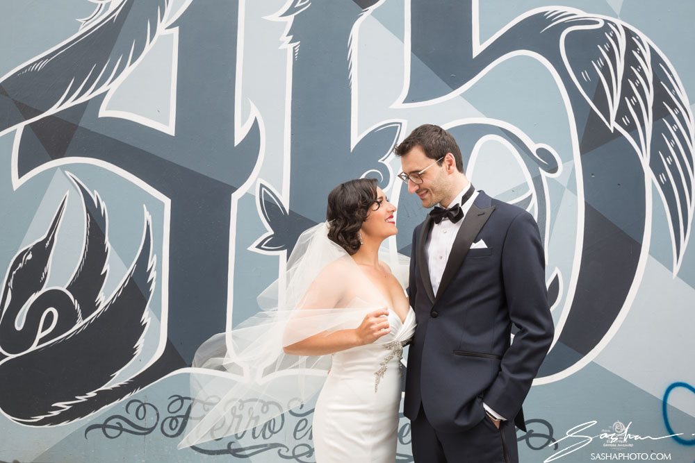 wedding couple in front of mural